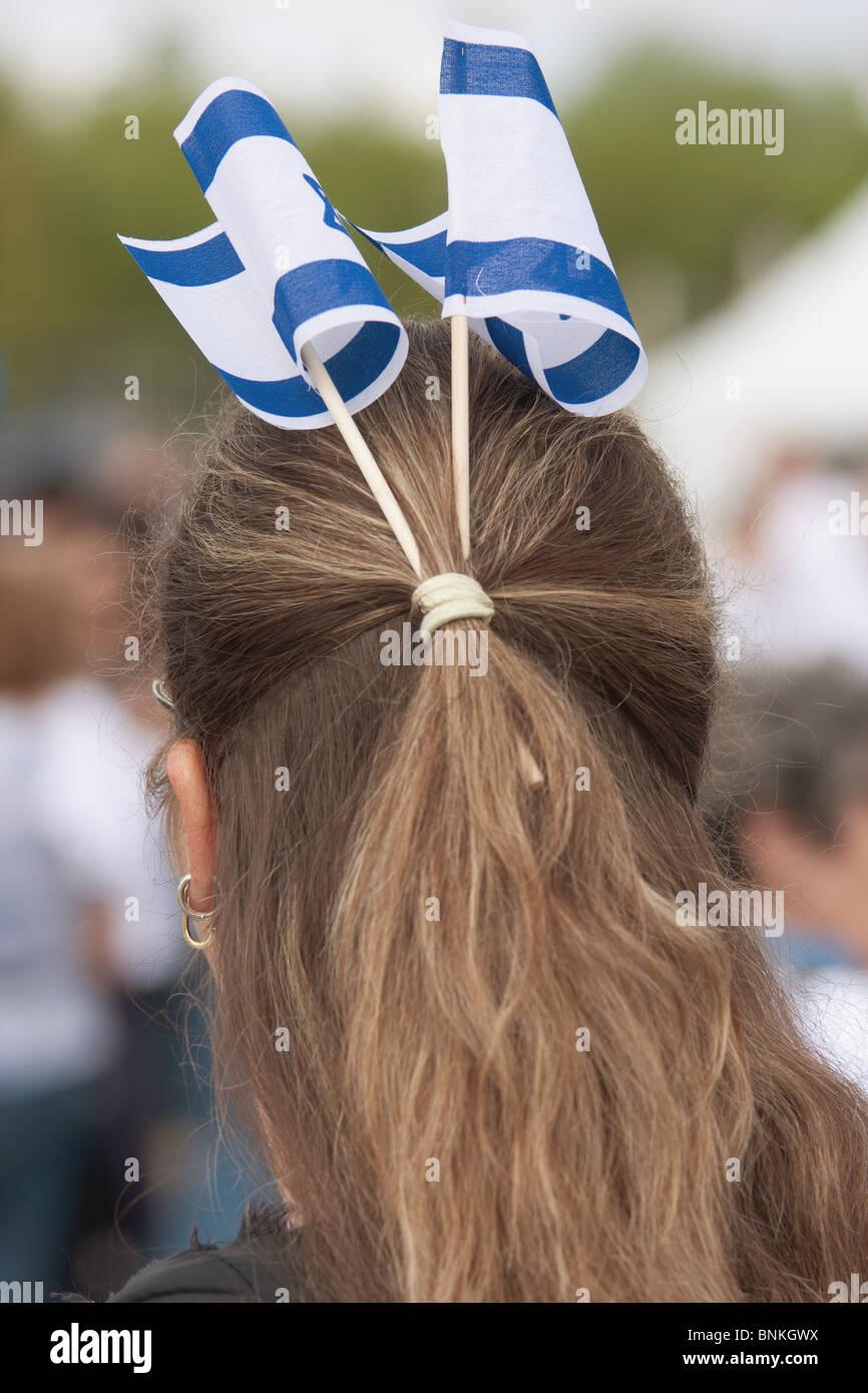 Women demonstrator with Israeli flags tucked in her hair - Stock Image