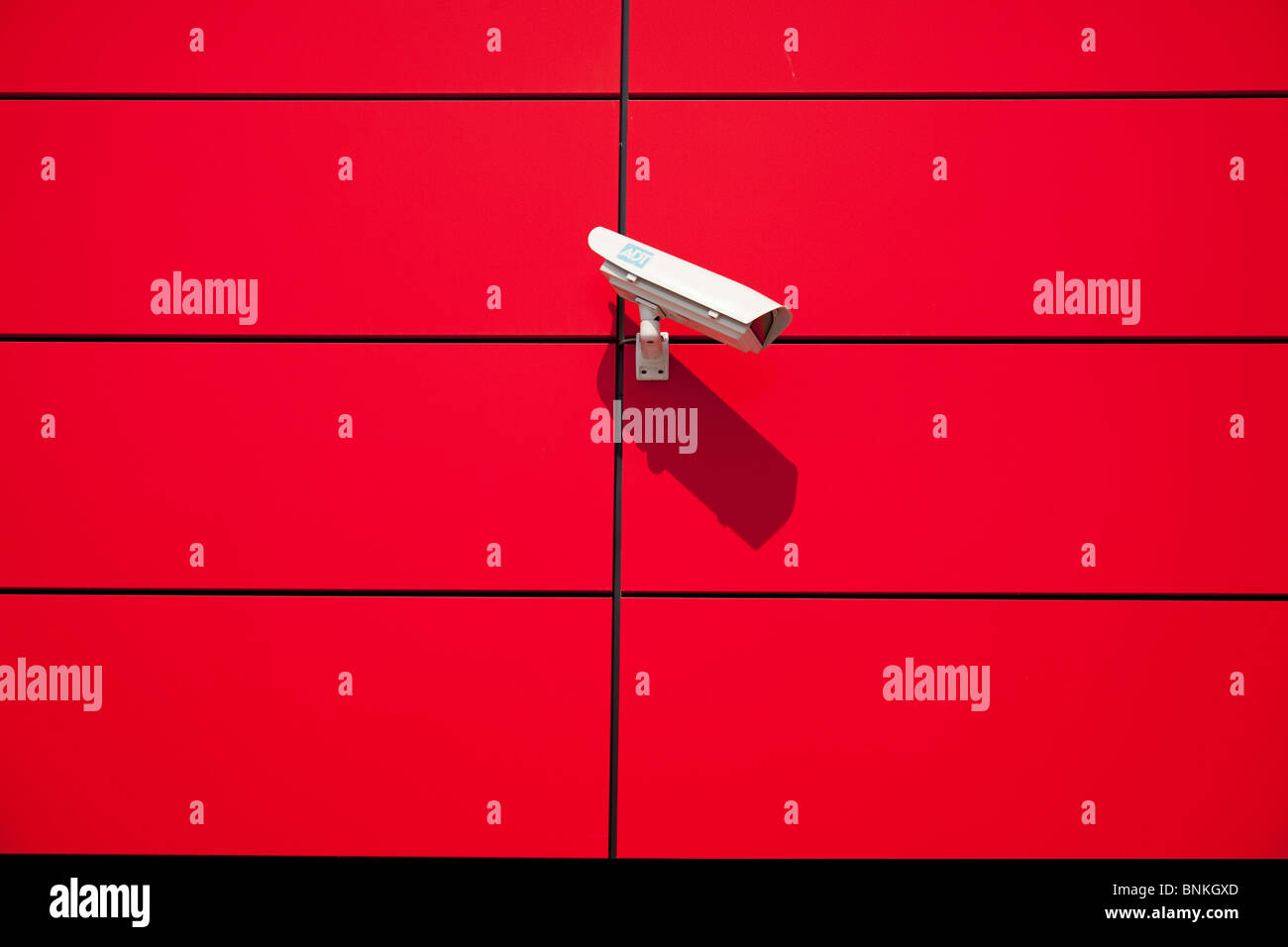 Surveillance camera at a red, modern house front - Stock Image