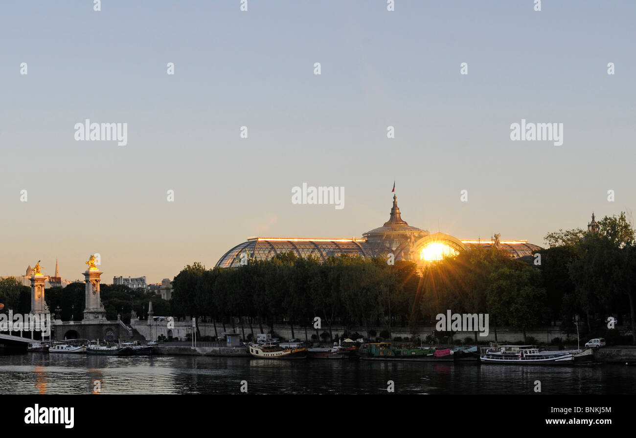 The Grand Palais in central Paris reflecting the rising sun: the 20th century architectural landmark is made of - Stock Image