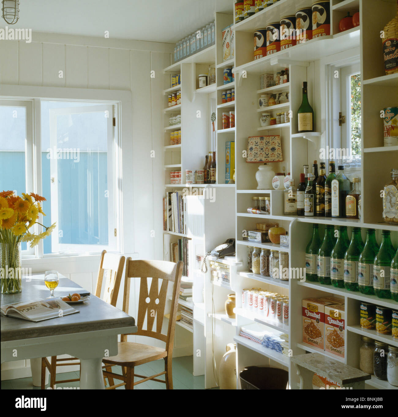 Wall of white shelves with bottles and cans in small white dining area of traditional kitchen Stock Photo