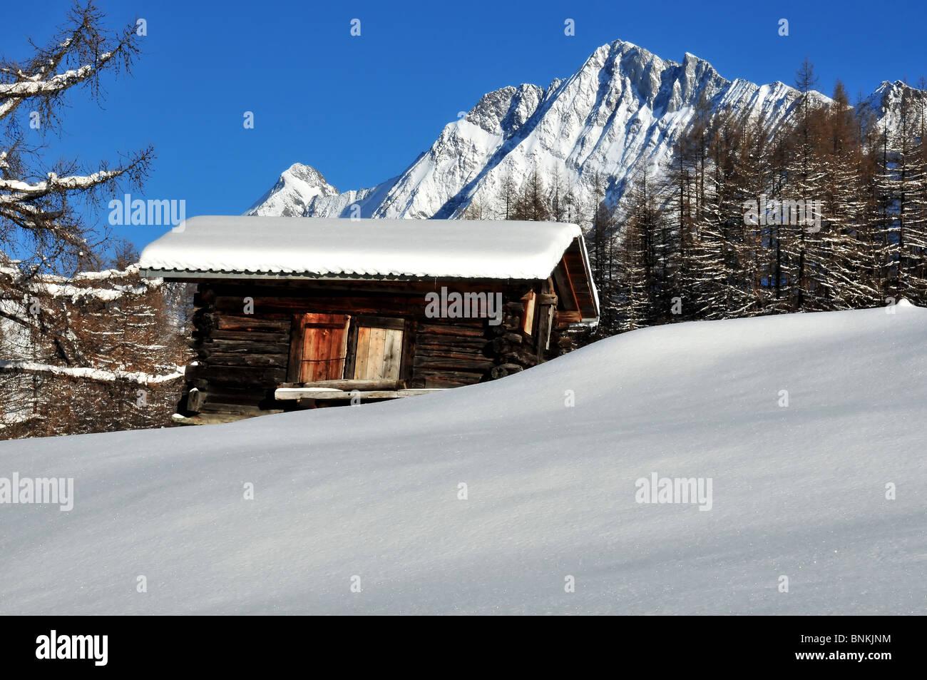 Switzerland Valais Blatter snow larch winter mountains Alps hut building construction glitter map card Swiss scenery - Stock Image