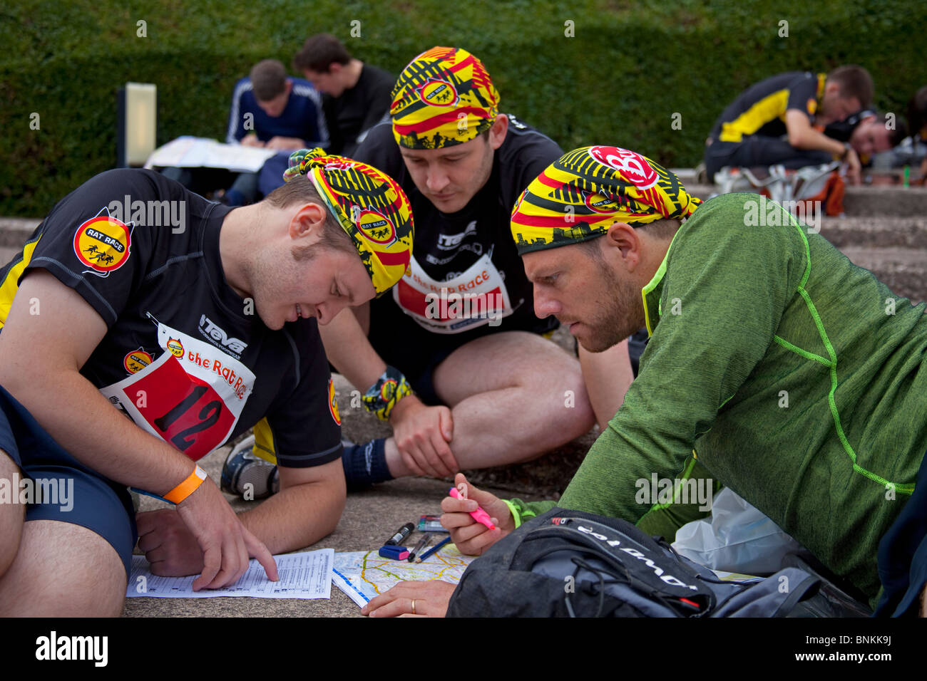 Male Rat Race competitors examine route map, Edinburgh Scotland UK Europe - Stock Image