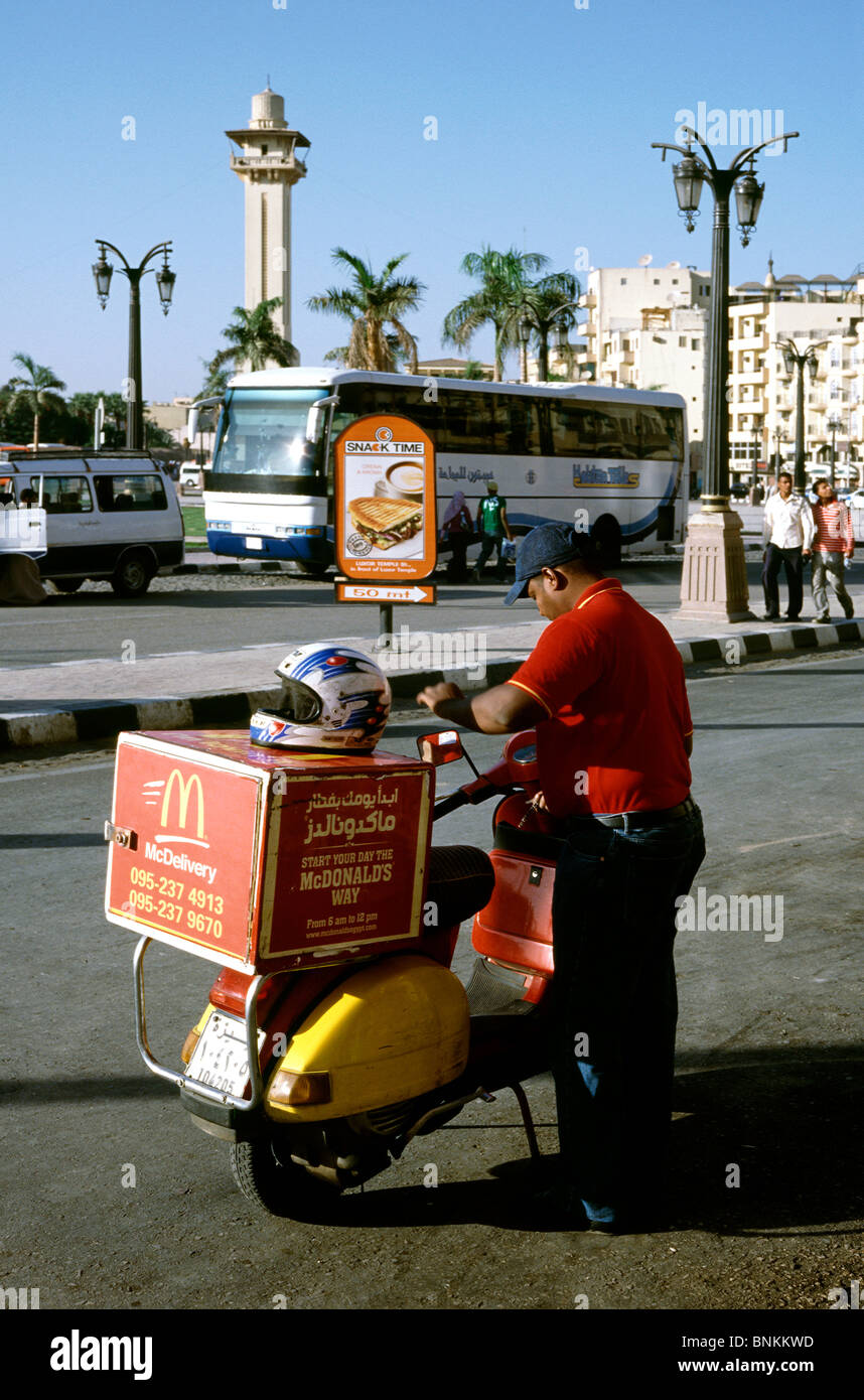 McDonald's employee and his fast food delivery scooter in Luxor in Upper Egypt. - Stock Image