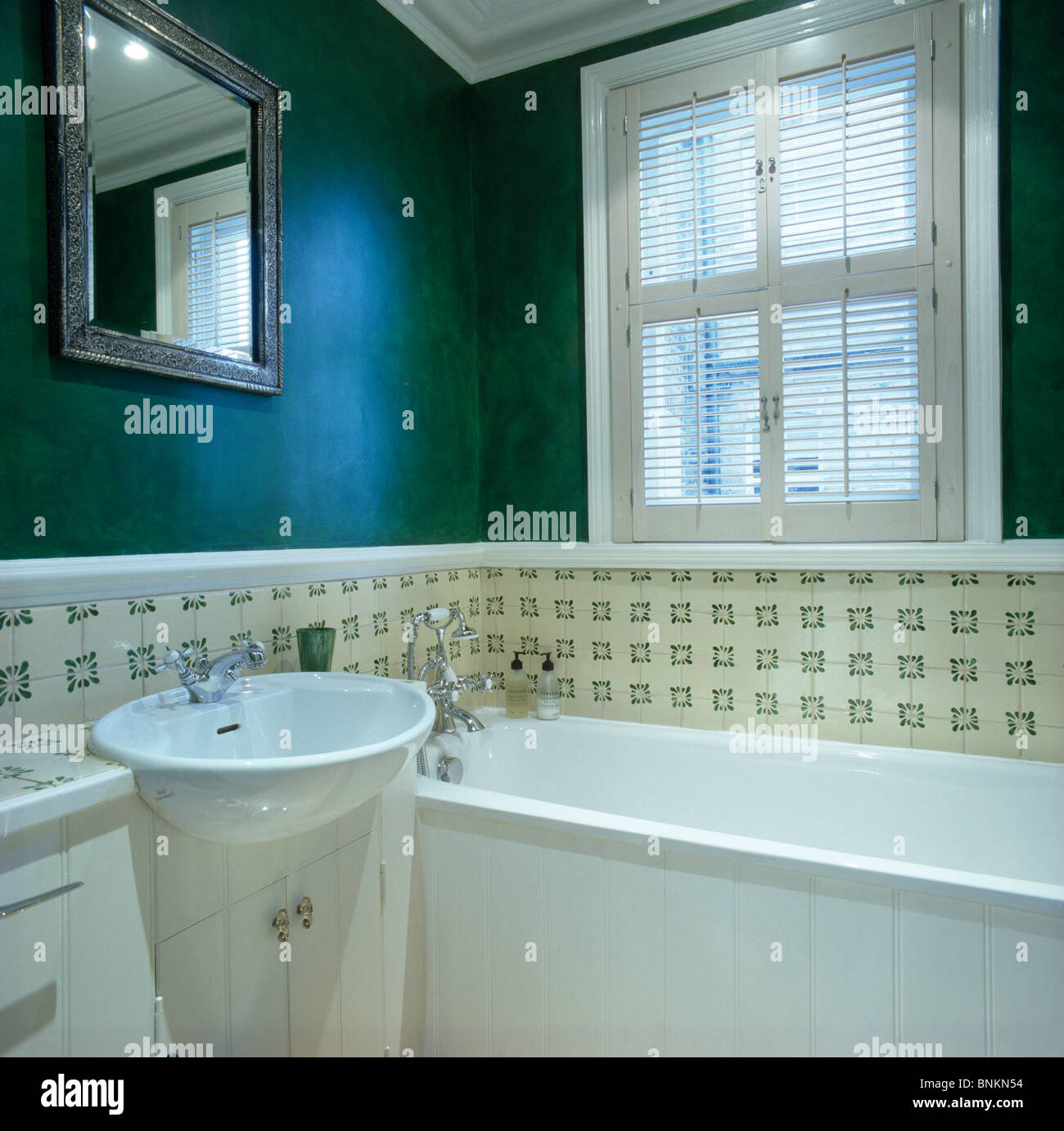 Plantation shutters on window above bath in modern green bathroom ...