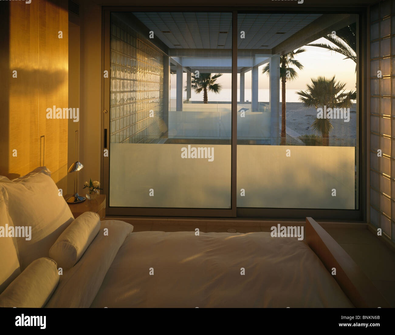 Sunlight on bed in modern coastal bedroom with sliding glass doors ...