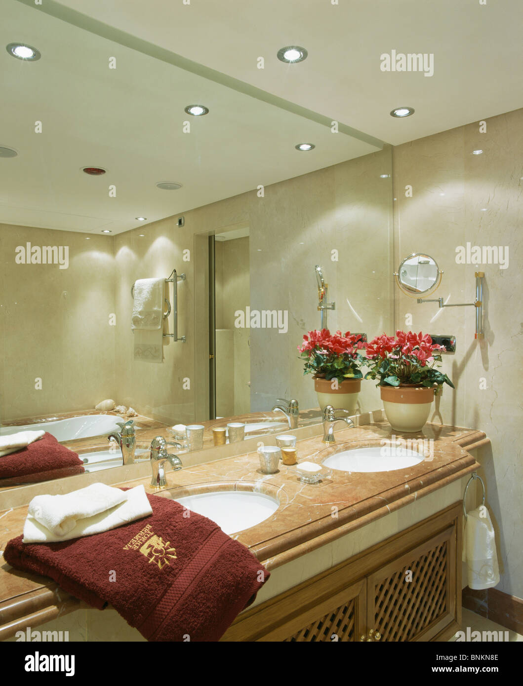 Mirrored wall above under-set basins in marble-topped vanity unit in modern bathroom with recessed lighting - Stock Image