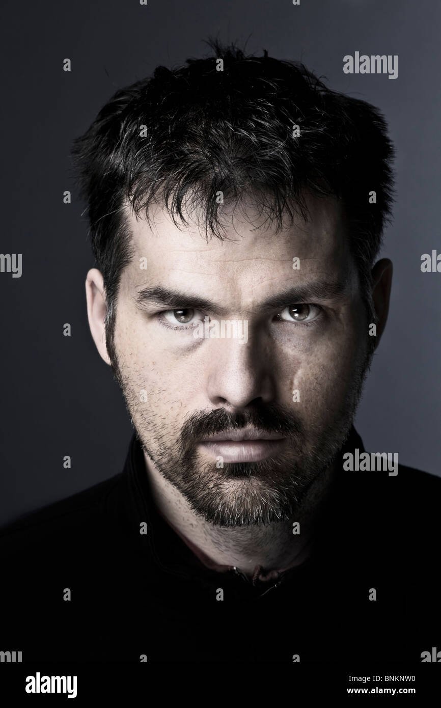A dark a portrait of unshaved man - Stock Image