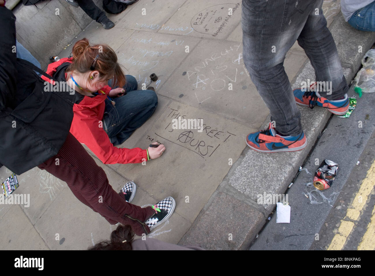 Girl writing  'This street is ours' on the pavement outside The Bank of England during G20 protest, London - Stock Image