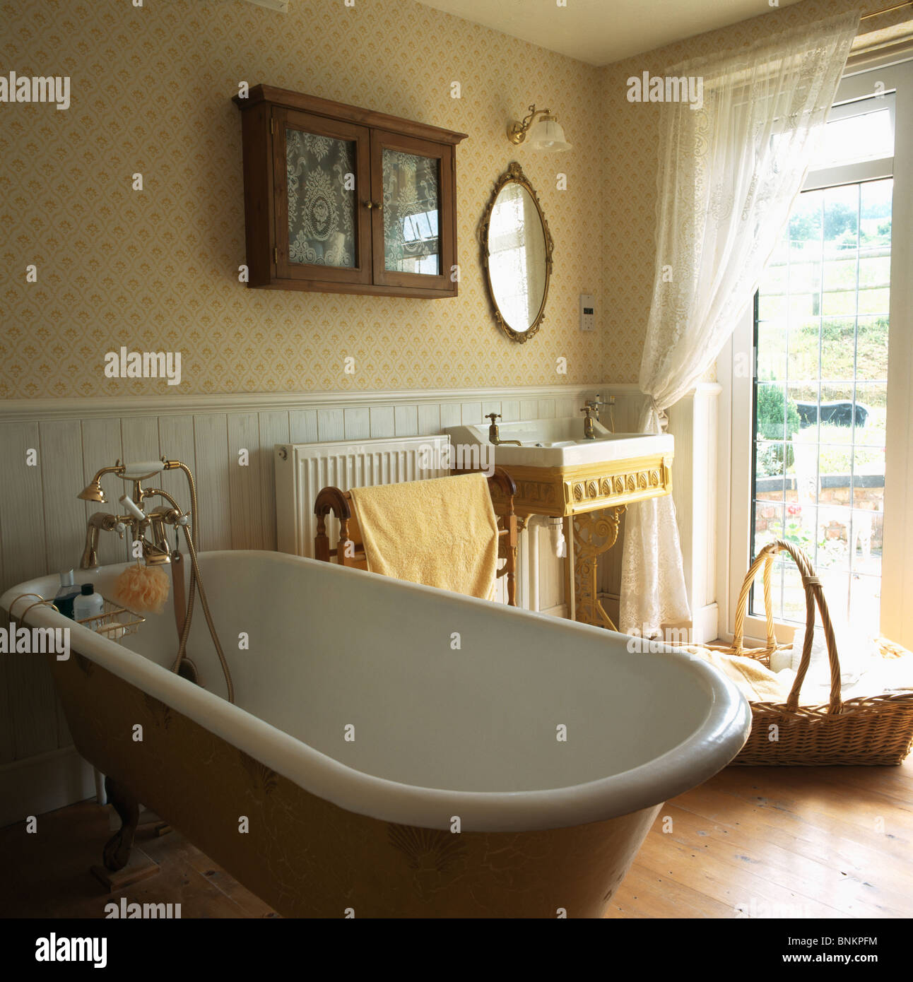 Patterned wallpaper and roll-top bath in traditional bathroom with ...