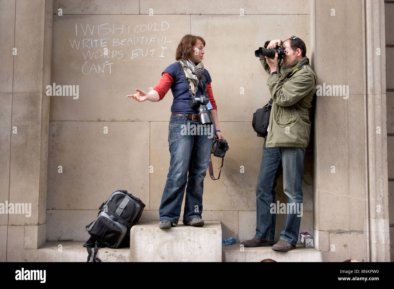 Photographers at G20 protest with graffiti chalked on the wall 'I wish I could write beautiful words but I can't' - Stock Image