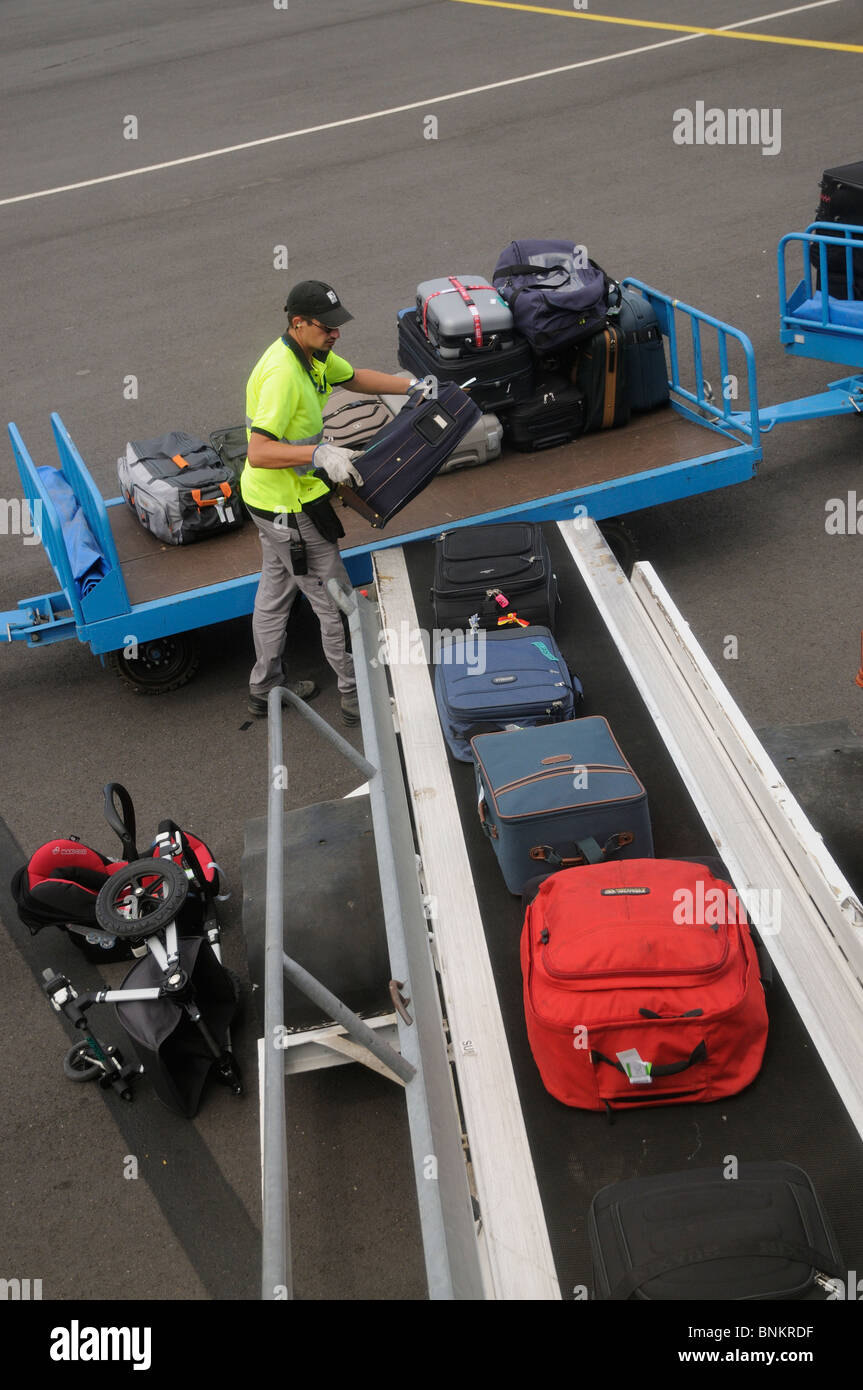 Airport baggage handler loading bags from a trolley onto an aircraft at Beziers International Airport southern France - Stock Image