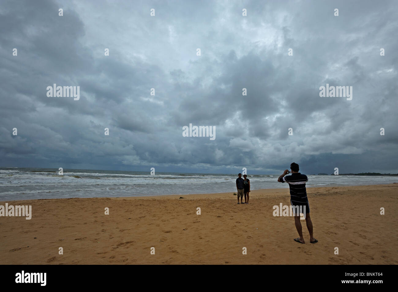 Tourists taking snap shots of each other in Bentota beach in Sri Lanka - Stock Image
