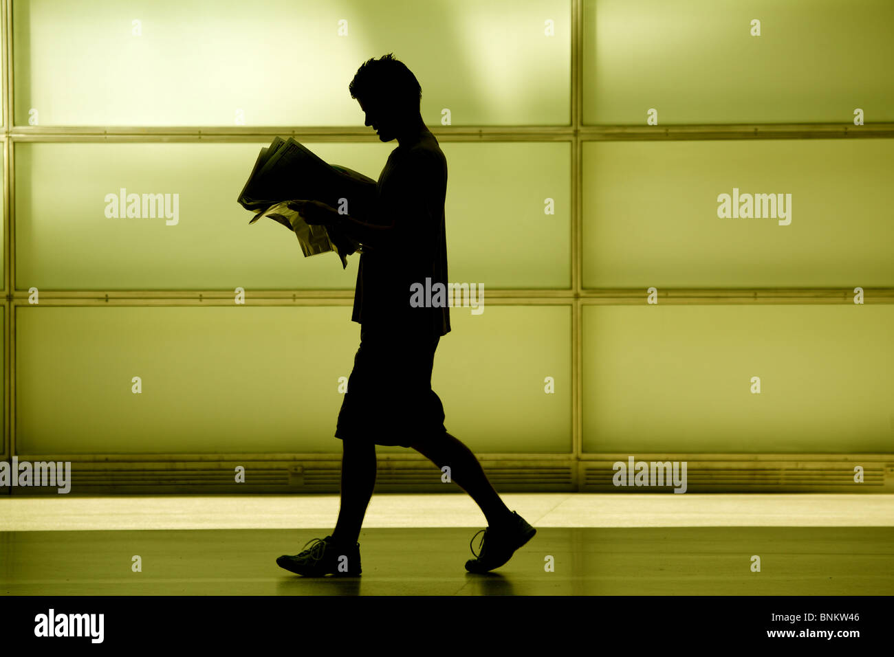 Young man walking and reading a newspaper - Stock Image