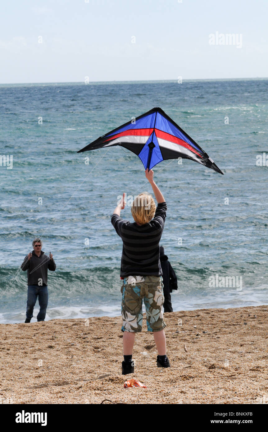 Boy letting go of a small kite with his dad having fun on the beach with the sea behind them - Stock Image
