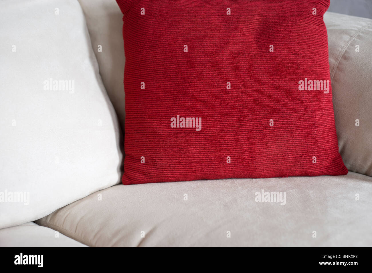 White and red pillows rest on the cushions of a couch in Corona, New Mexico. - Stock Image