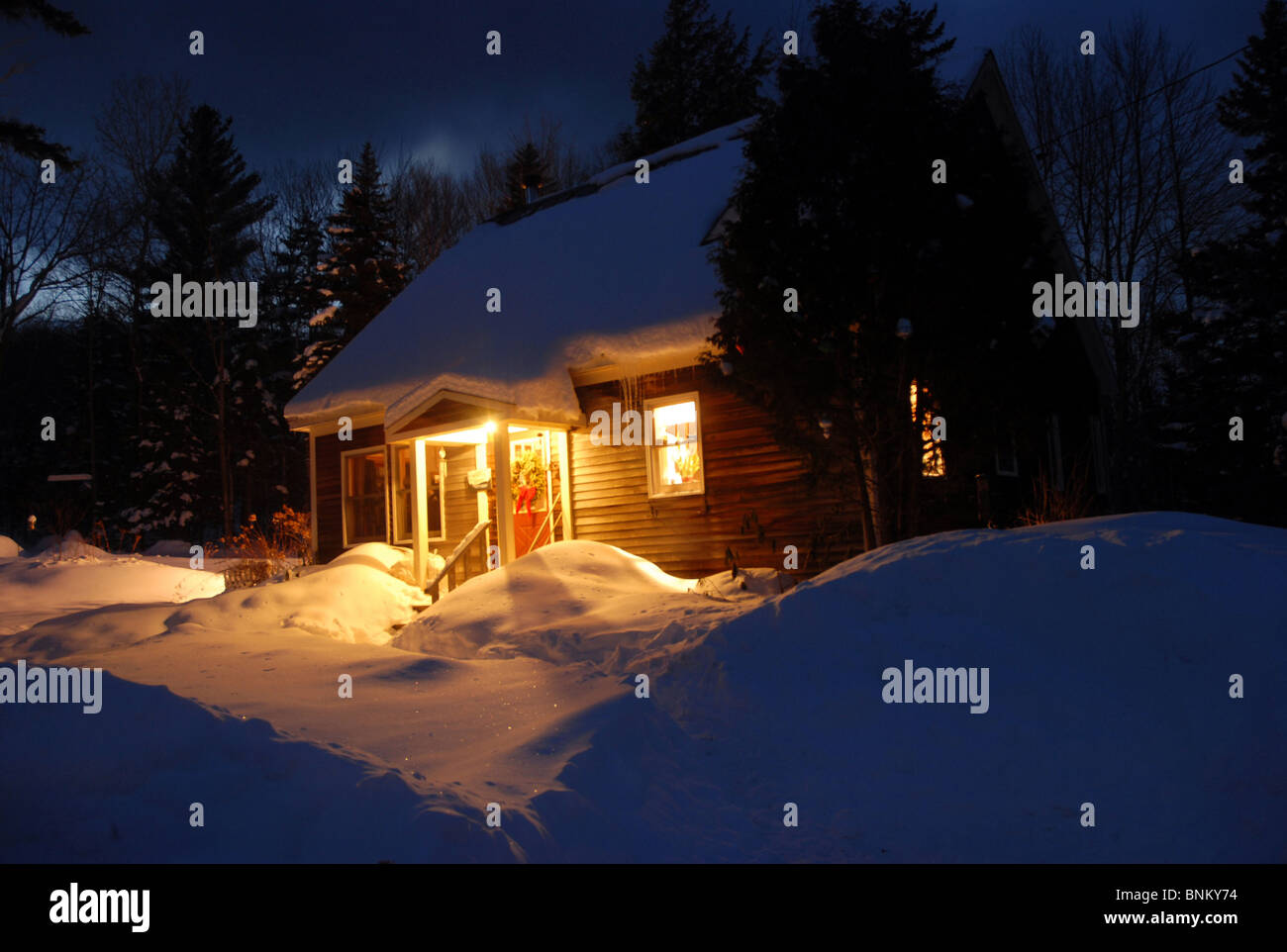 A lights reflects off the snow during this winter evening in Vermont. - Stock Image