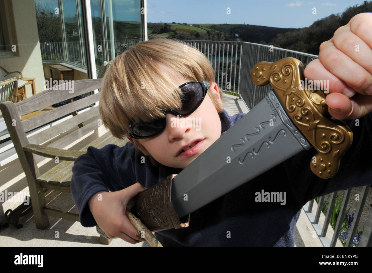 Fair-haired boy wearing sunglasses and playing with a plastic sword and scabbard outside by a bench. - Stock Image