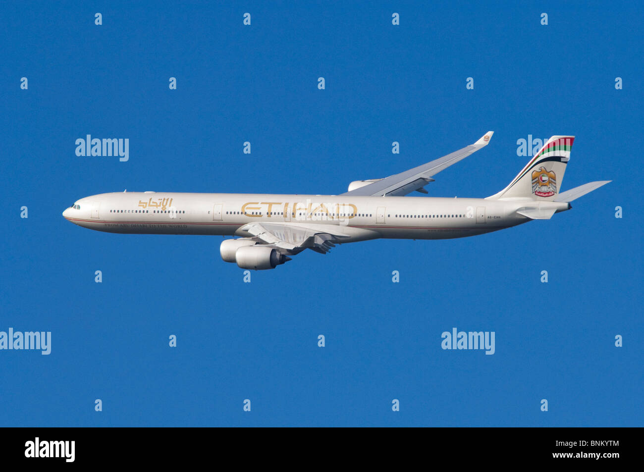 Airbus A340 operated by Etihad climbing out after take off from London Heathrow Airport, UK. - Stock Image