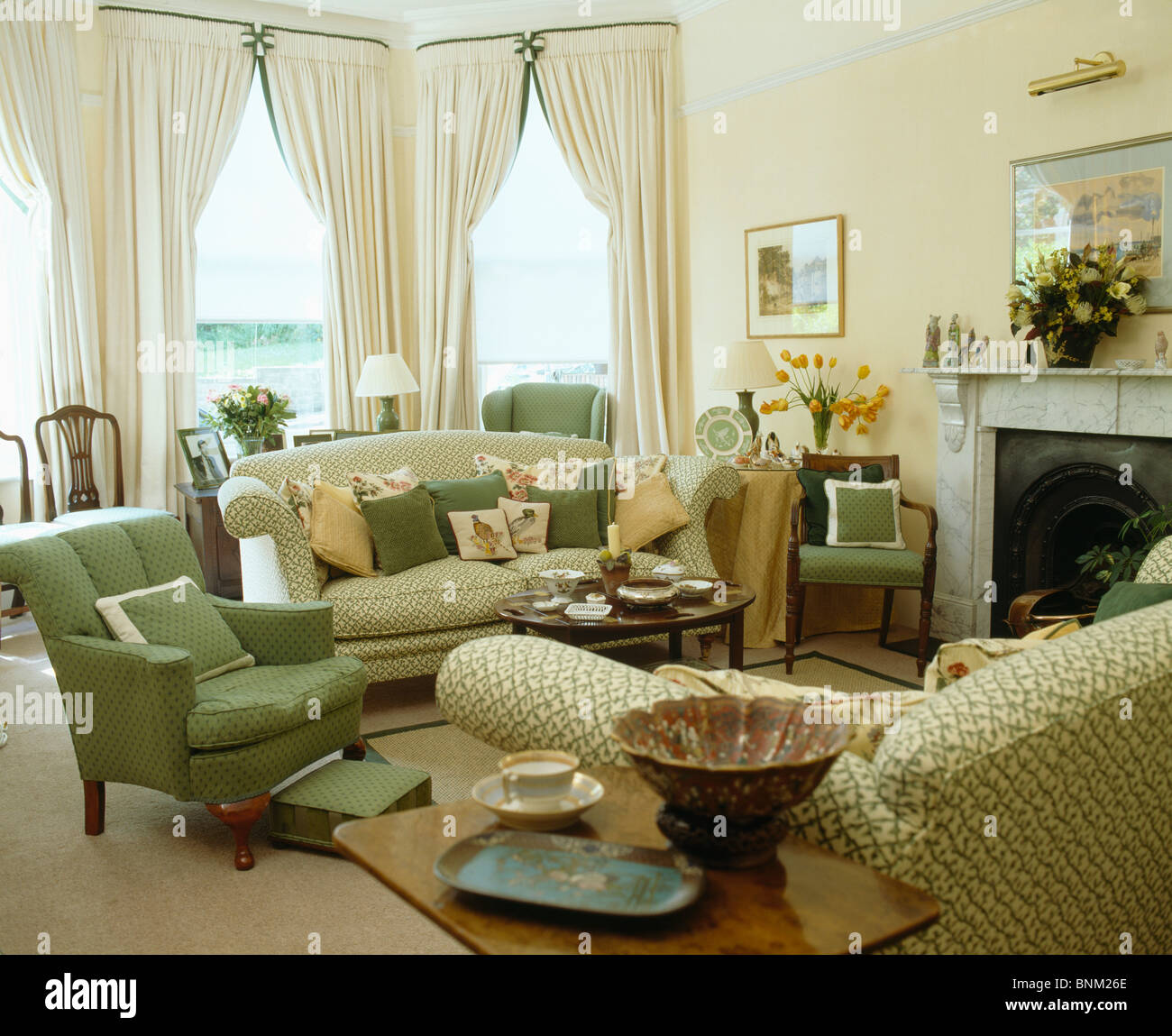 Green Armchair And Sofa Piled With Cushions In Traditional Living Stock Photo Alamy