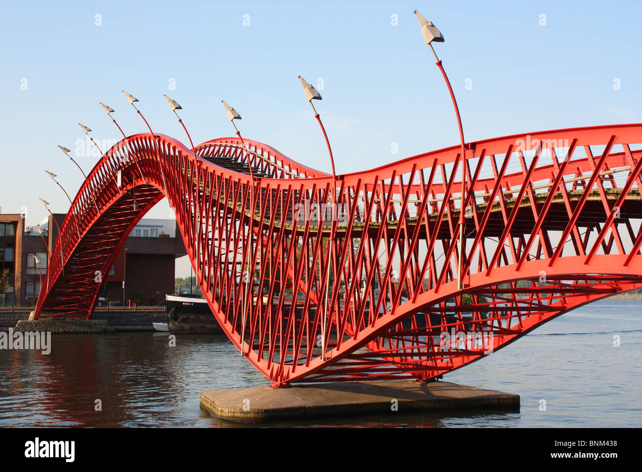 Modern red bridge from Borneo Island to Sporenburg peninsula in the Amsterdam Eastern Docklands. - Stock Image