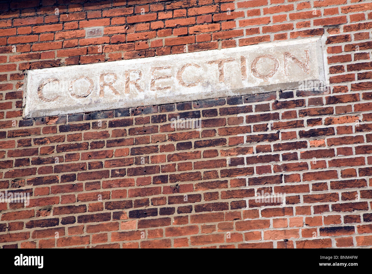 Correction sign in brick wall - Stock Image
