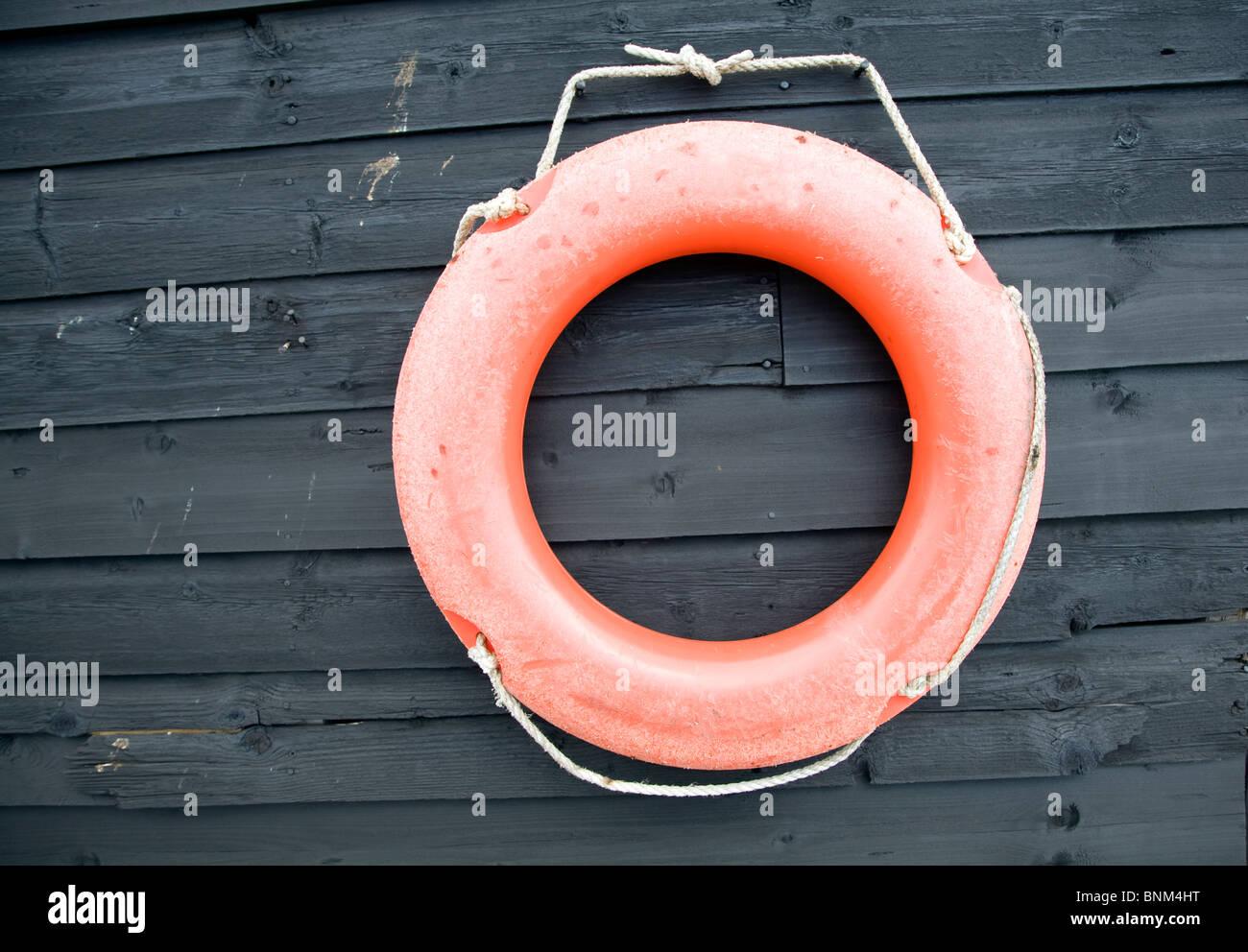 Orange red life saving ring on black wooden shed - Stock Image