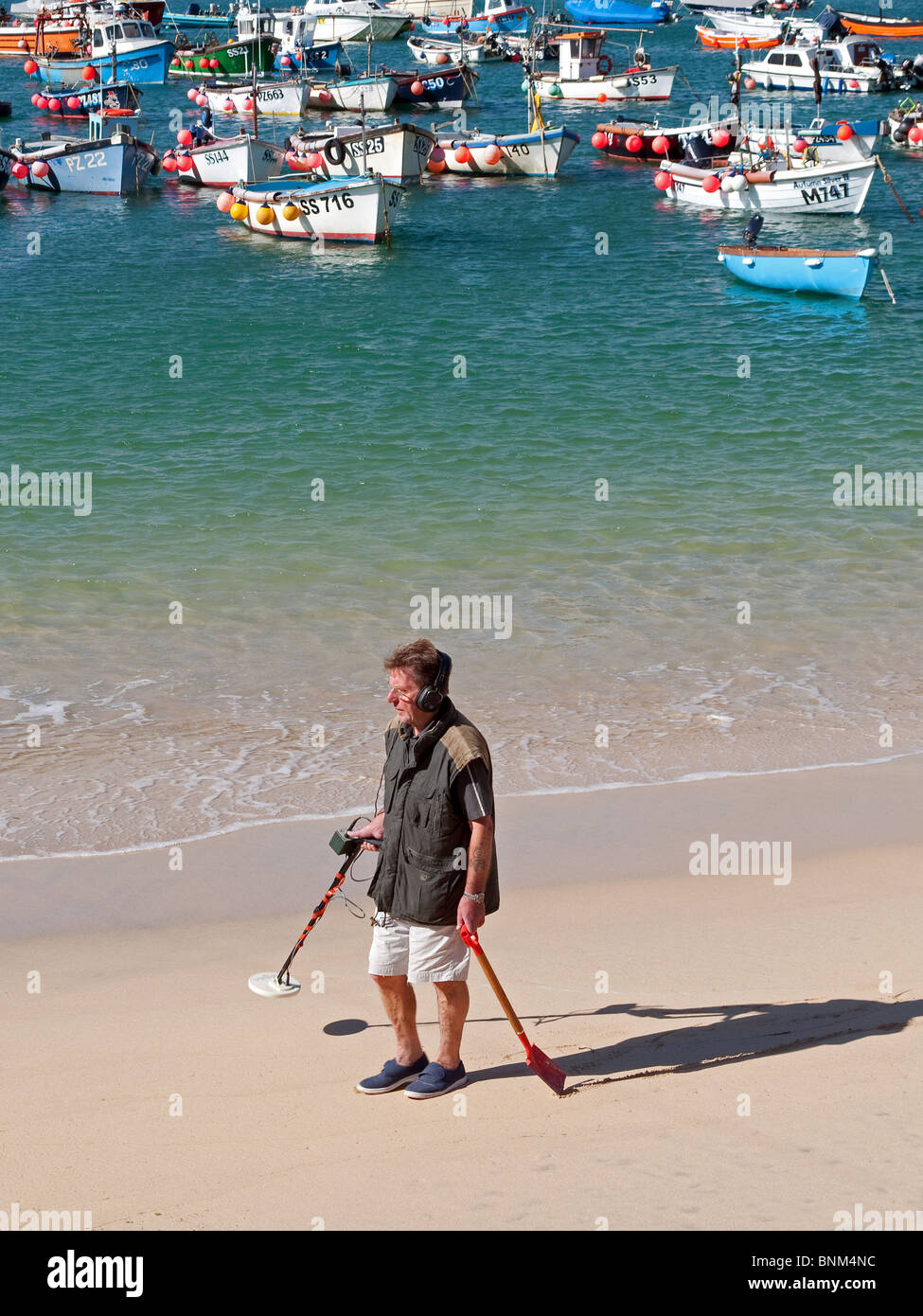 a man using a metal detector on the beach at st.ives in cornwall, uk - Stock Image