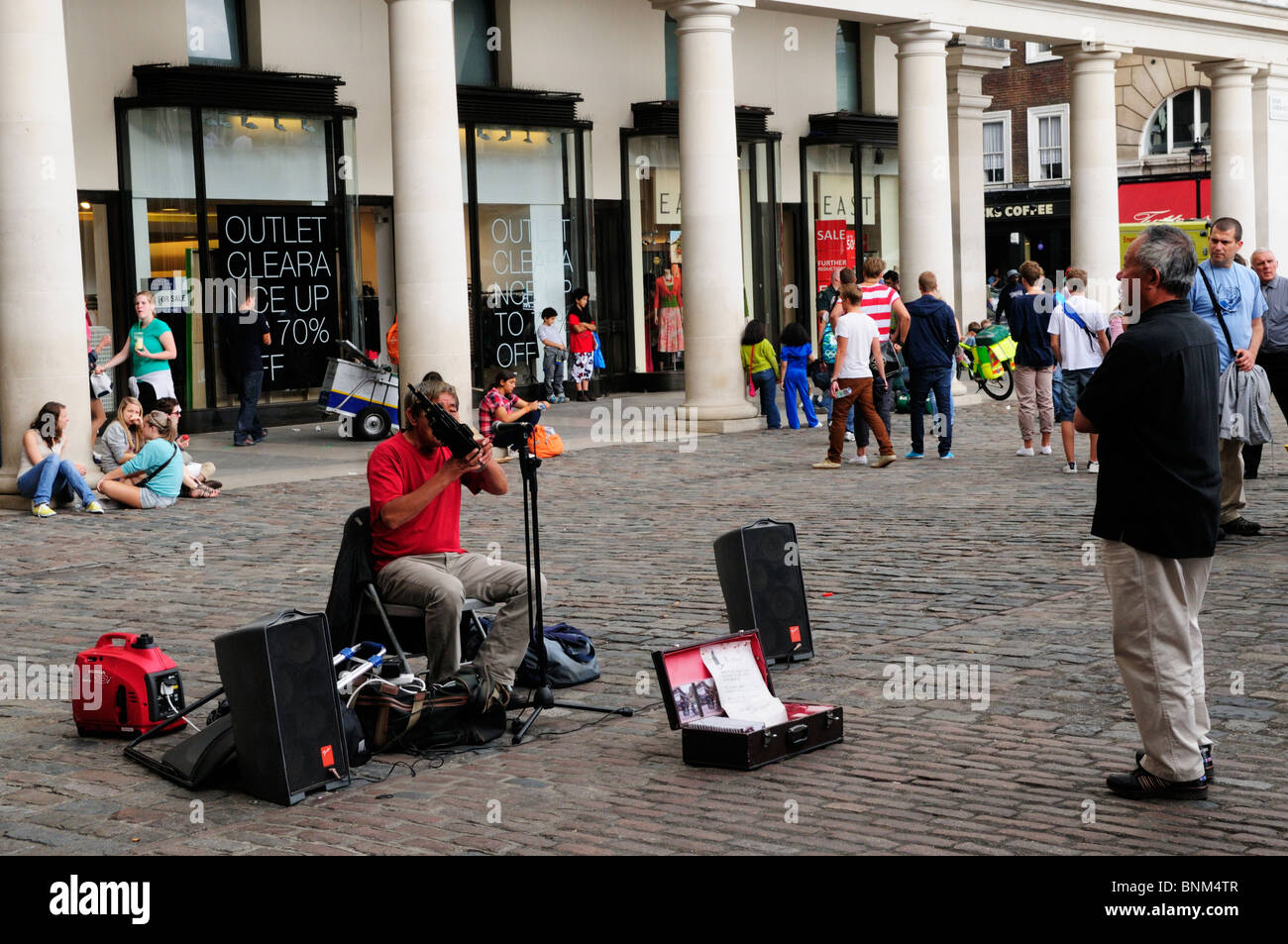 Chinese Street Musician Busker playing a Sheng wind instrument, Covent Garden Piazza, London, England, UK - Stock Image