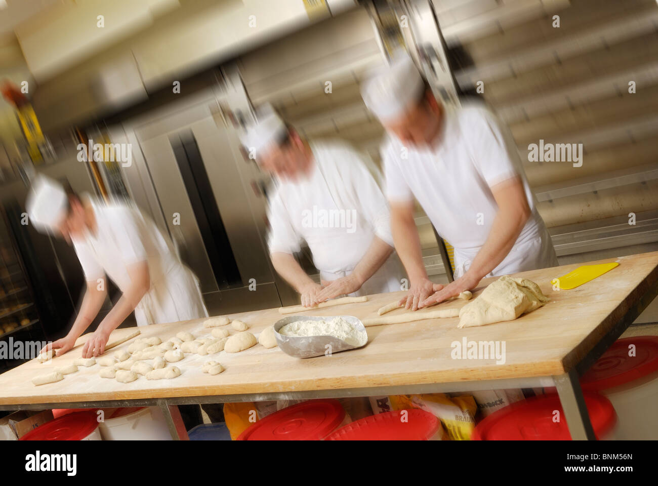 three baker, blurred,  forming cakes out of pastry - Stock Image