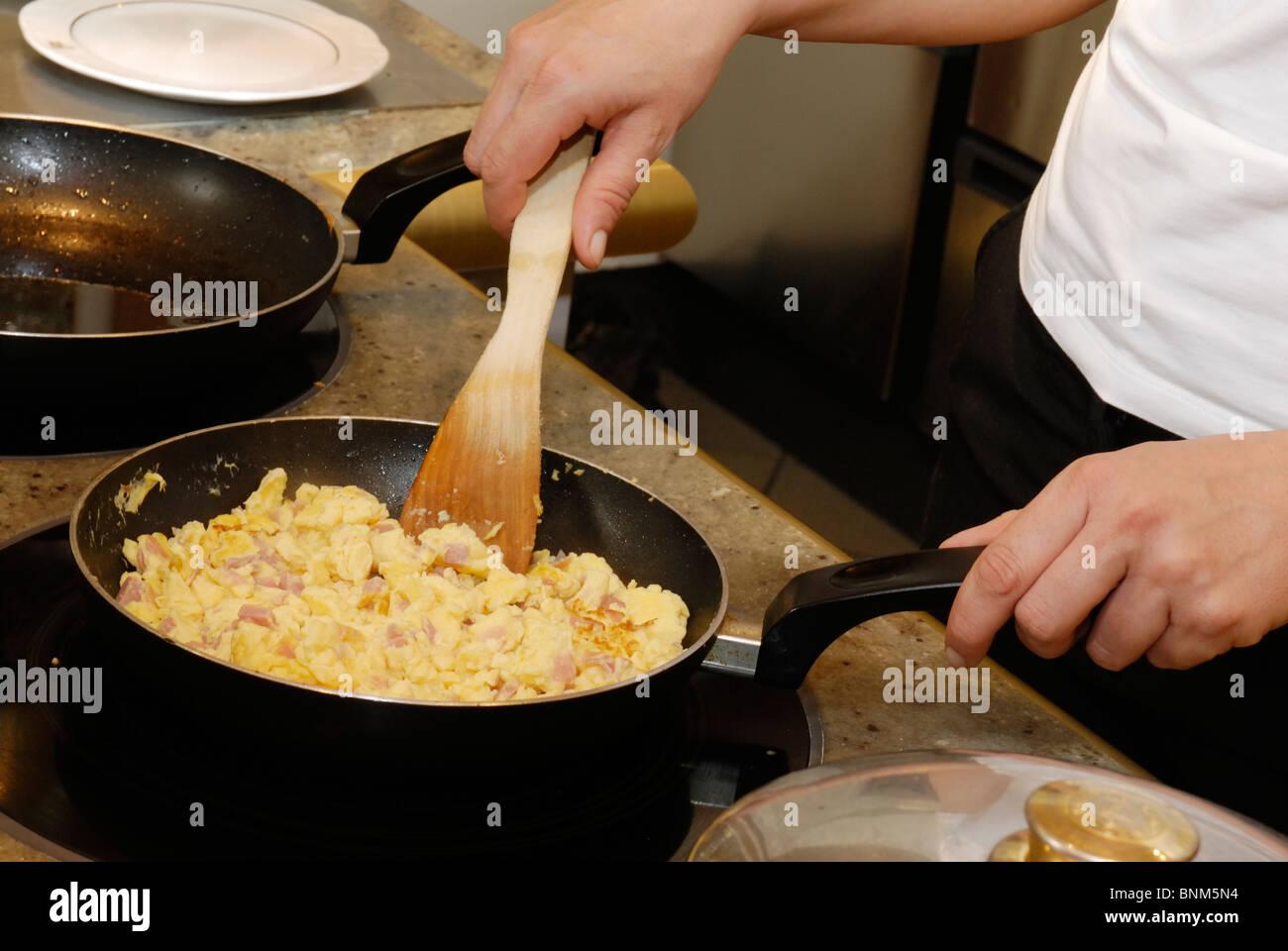 cook preparing scrambled eggs in a pan - Stock Image