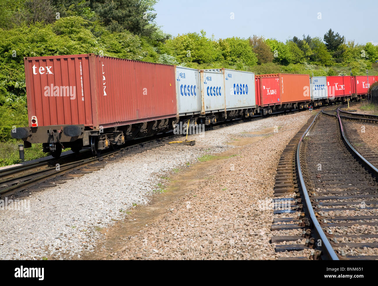 Railway freight train carrying containers rail lines rear view - Stock Image