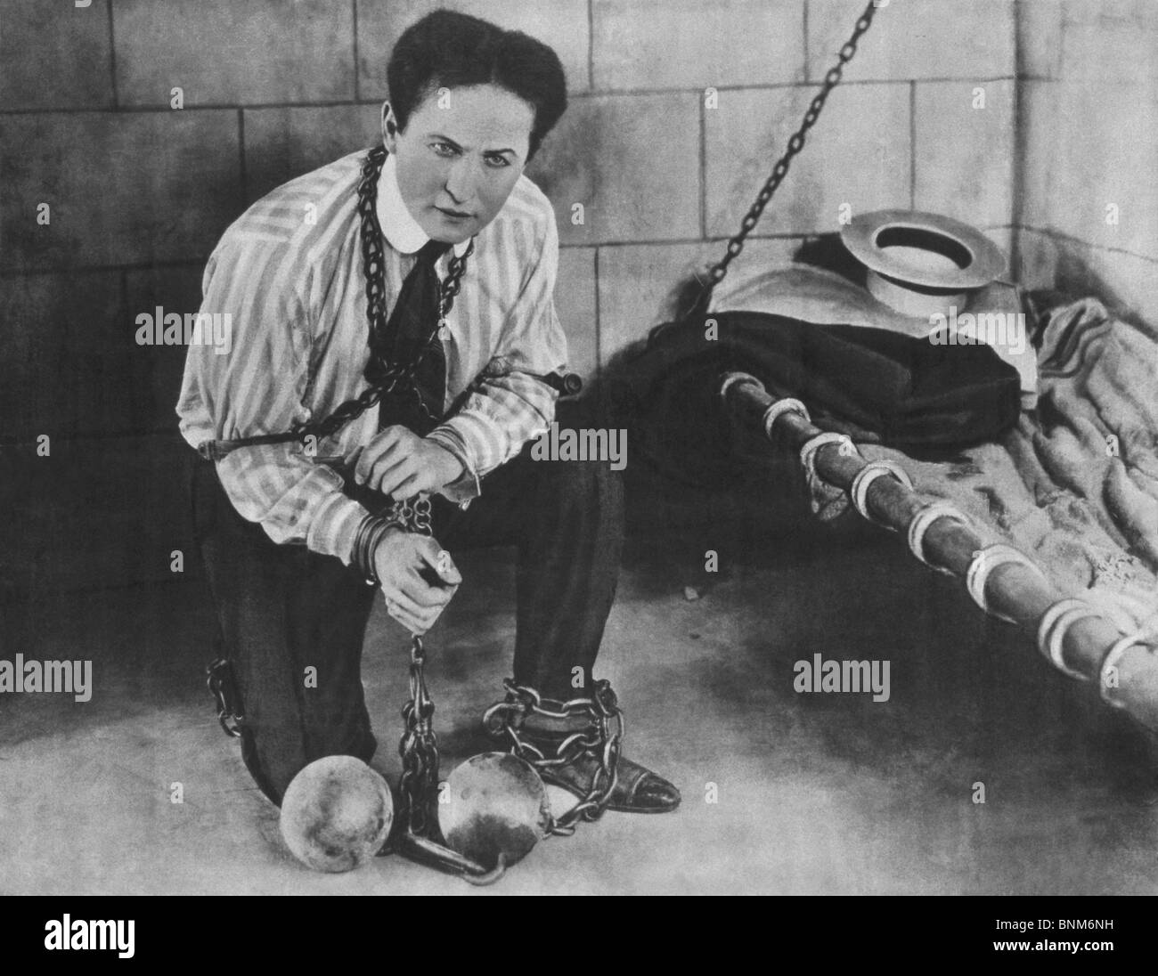 Promotional photo c1898 of magician + escapologist Harry Houdini (1874 - 1926) restrained in chains and locked in Stock Photo