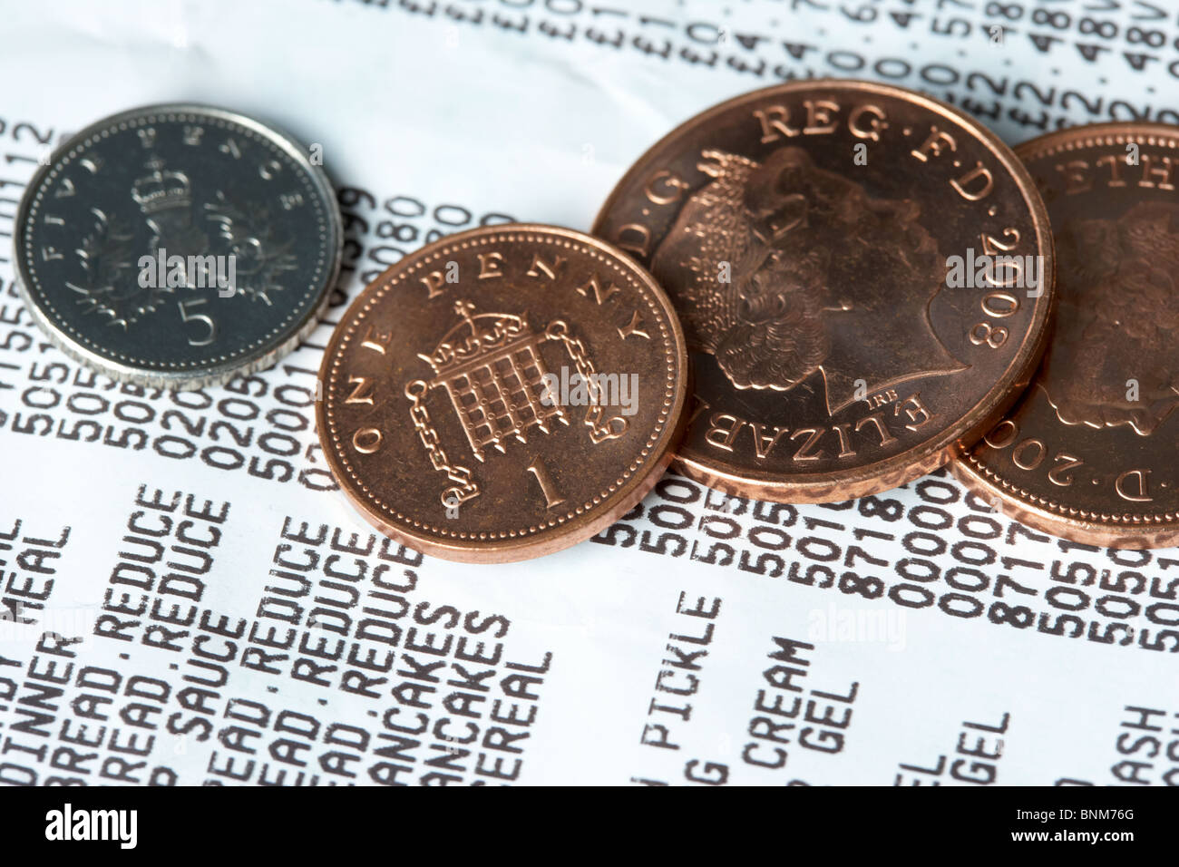 supermarket till receipt showing reduced items and british coins pennies Stock Photo