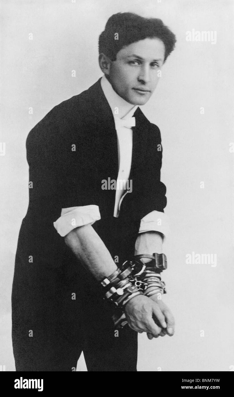 Portrait photo circa 1905 of magician and escape artist Harry Houdini (1874 - 1926) wearing multiple sets of handcuffs. Stock Photo
