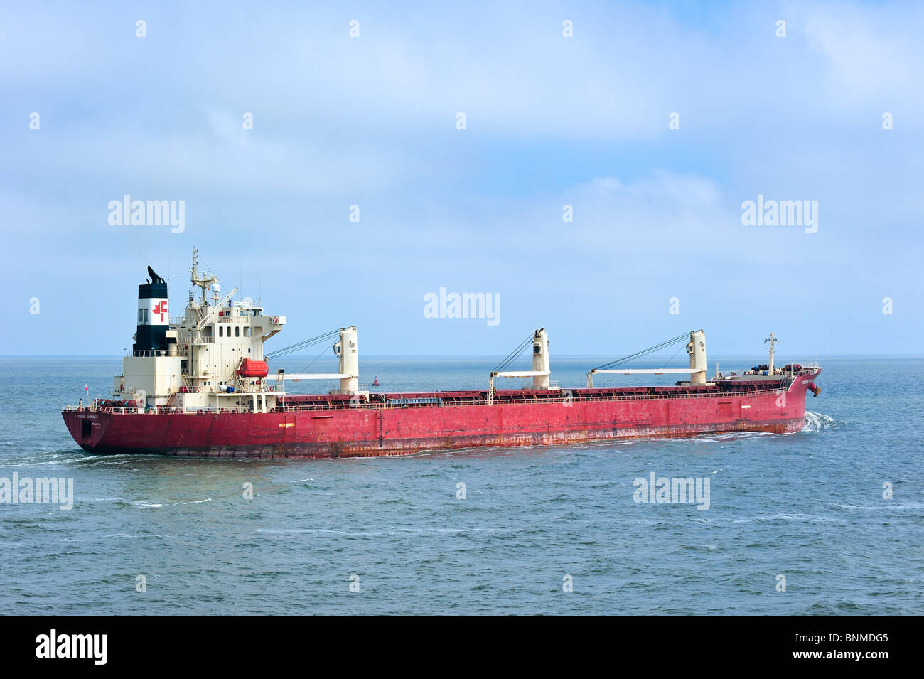 Red cargo ship / bulk carrier / freighter at the North Sea, Europe - Stock Image
