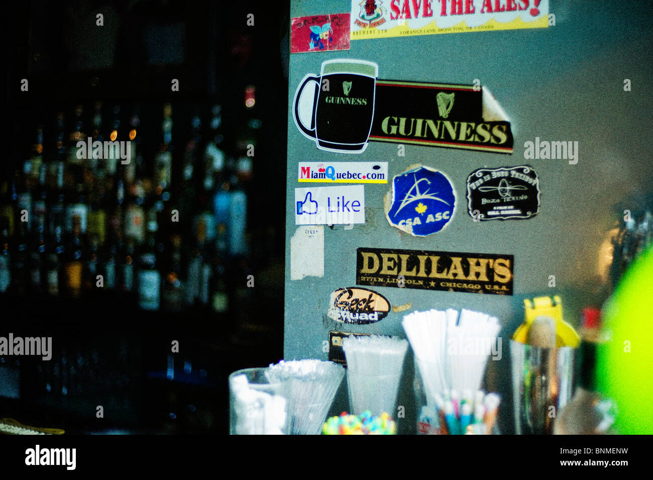 Stickers on bar cooler with rows of bottles behind bar. - Stock Image