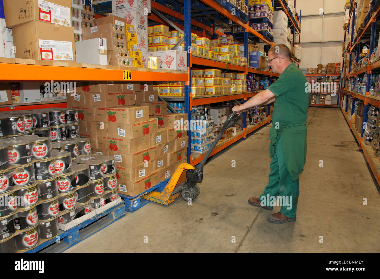Warehouse worker in green overall lifting a pallet in a dry goods warehouse. - Stock Image
