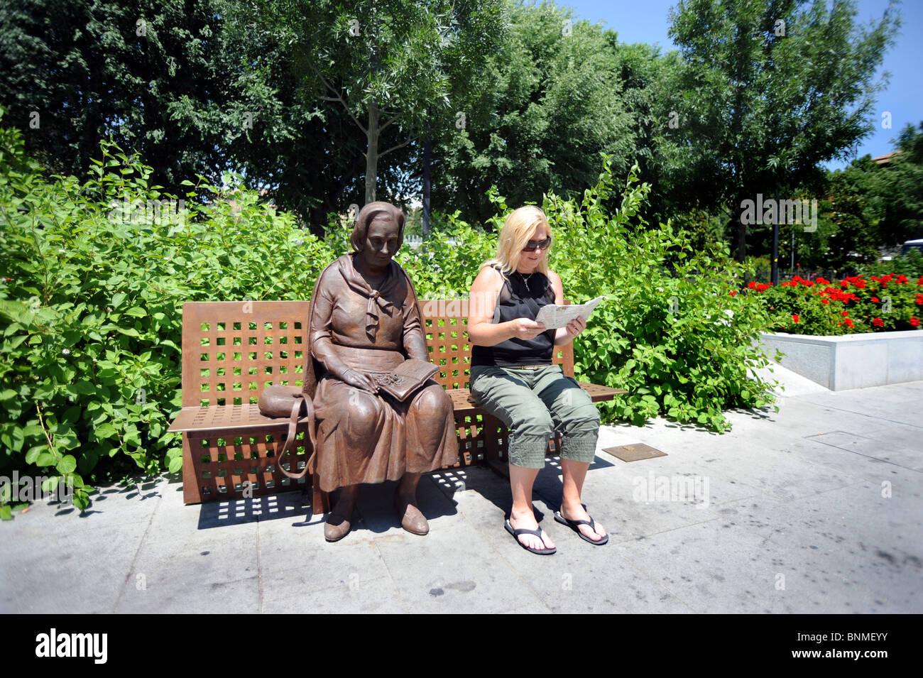 A tourist sits next to a sculpture of Elena Martin Vivaldi  by Jose A. Castro Vilchez on the Avda de le Constitucion - Stock Image