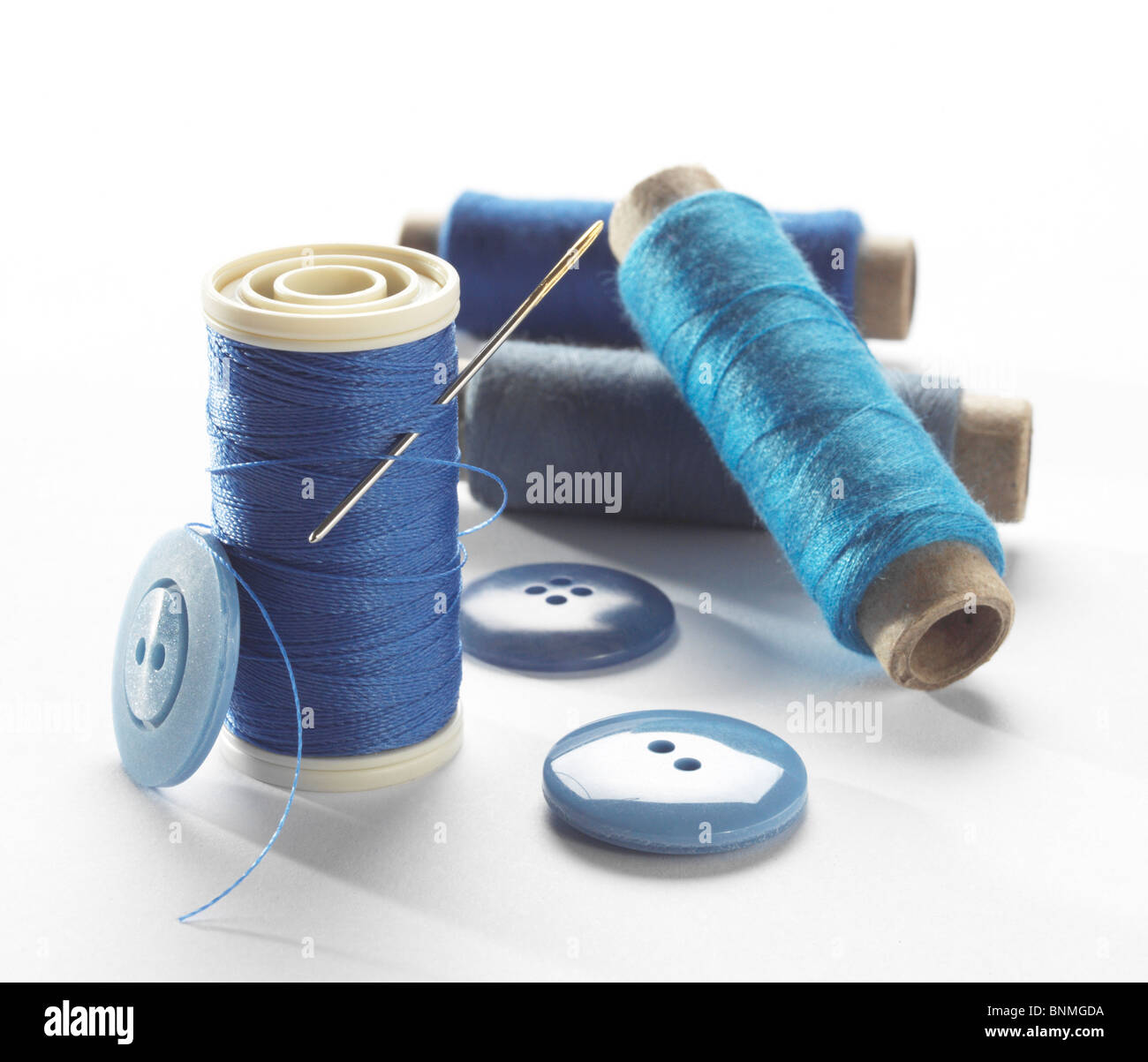 blue thread,buttons and needle - Stock Image