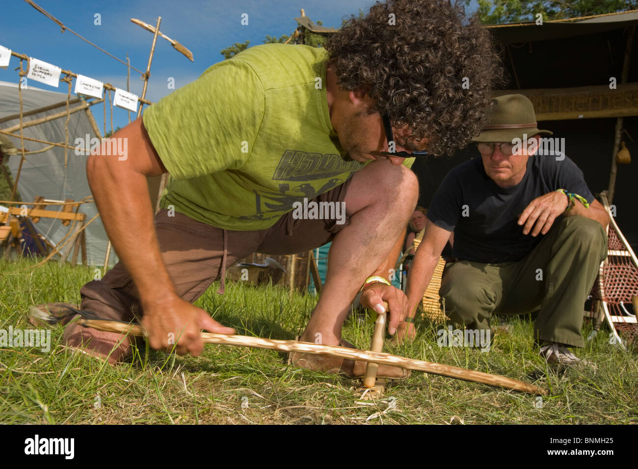 Wilderness survival expert teaches how to start a fire using a bow and friction to create heat at the Glastonbury - Stock Image