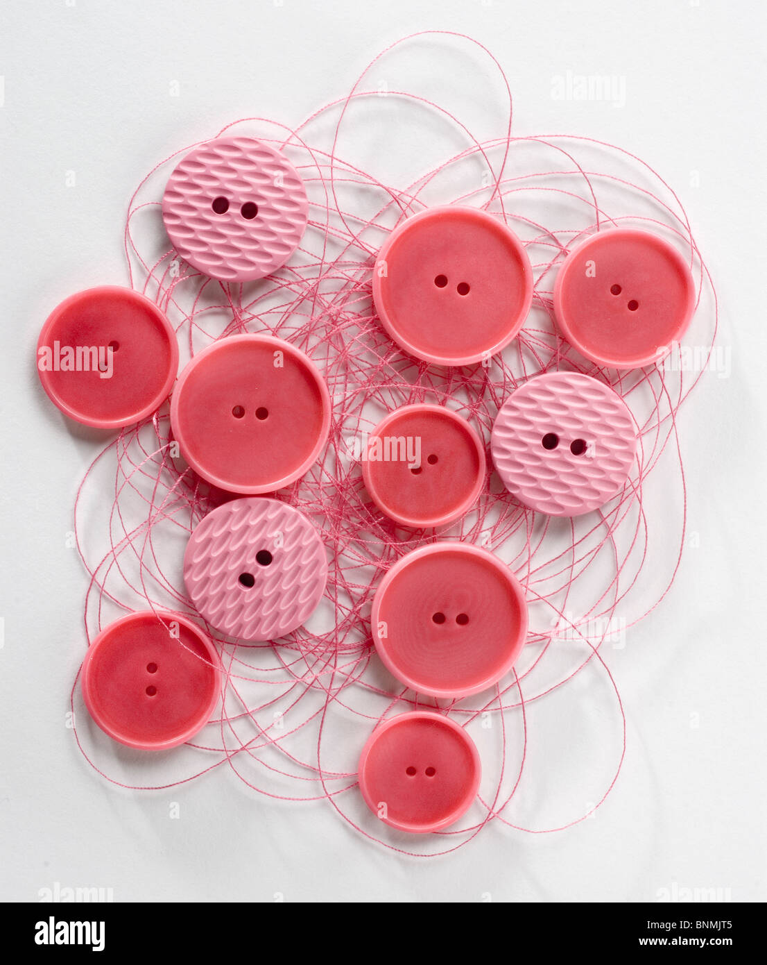 red buttons on red thread cut out - Stock Image