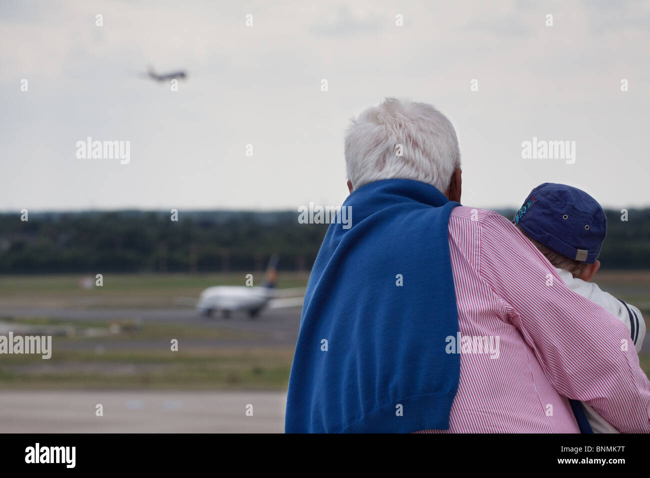 Grandfather and boy watch aeroplanes at airport - Stock Image