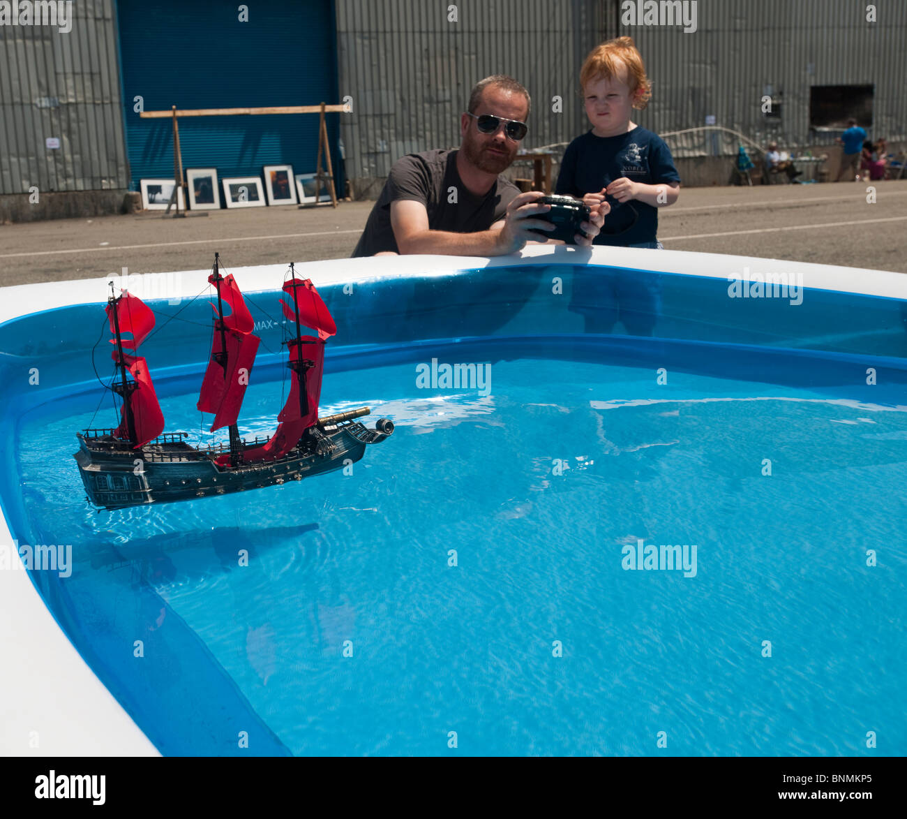 A family uses a radio control to maneuver a radio controlled toy boat in New York - Stock Image