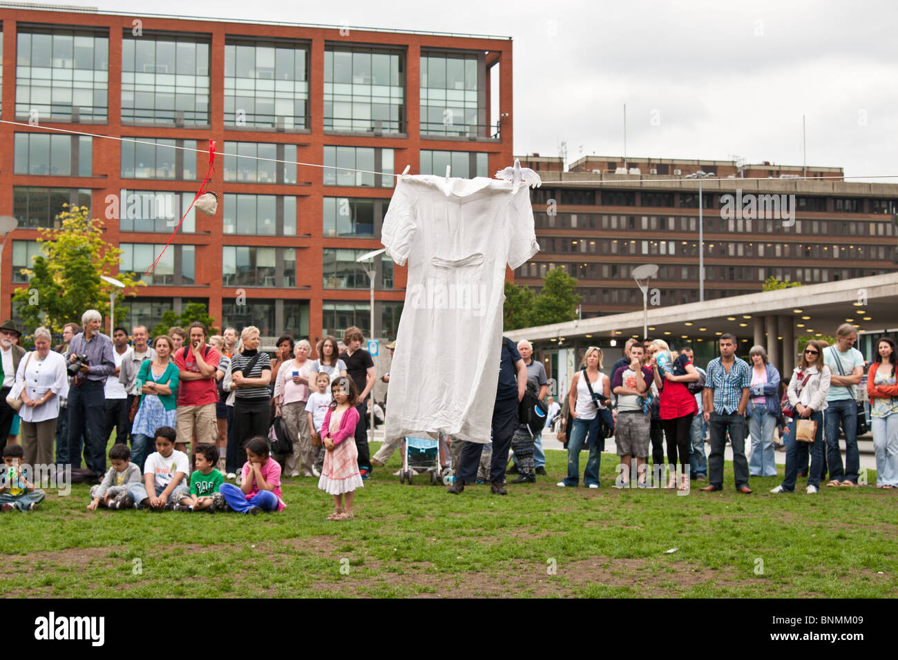 White dress hanging from above grass a line in an urban environment - Stock Image