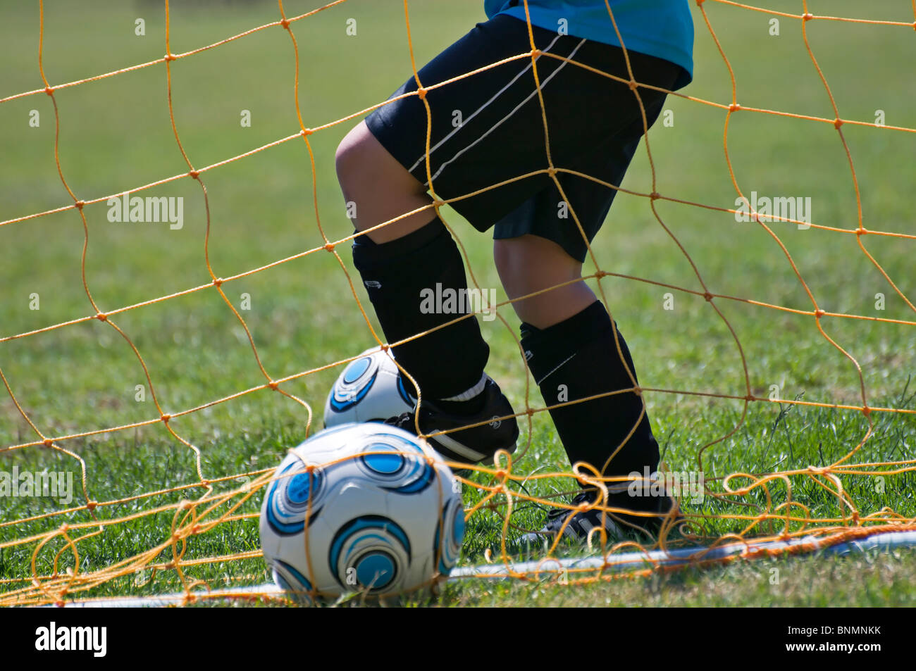 A child at soccer camp retrieves the ball out from under the net during practice. - Stock Image
