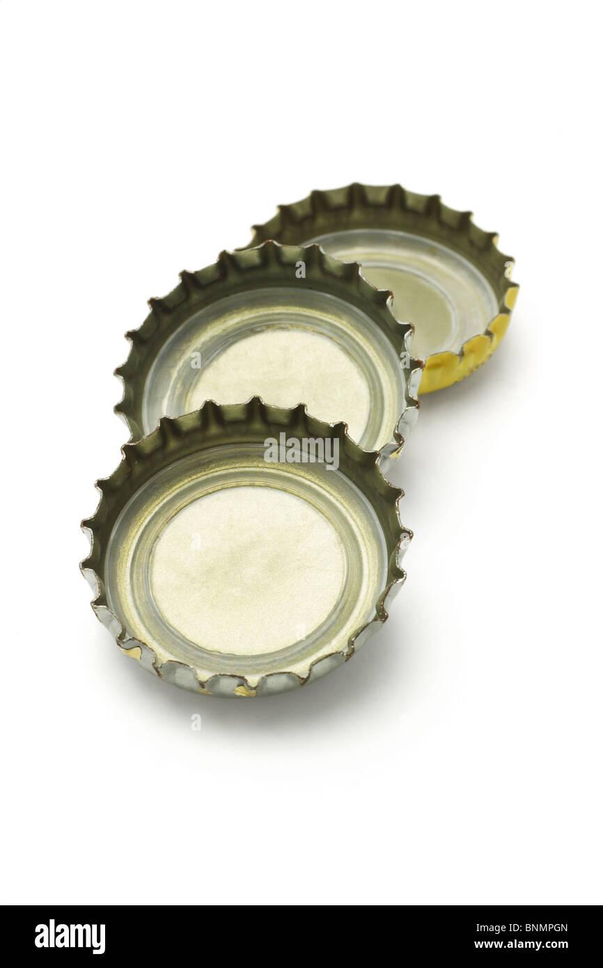 Three bottle caps lying on white background - Stock Image