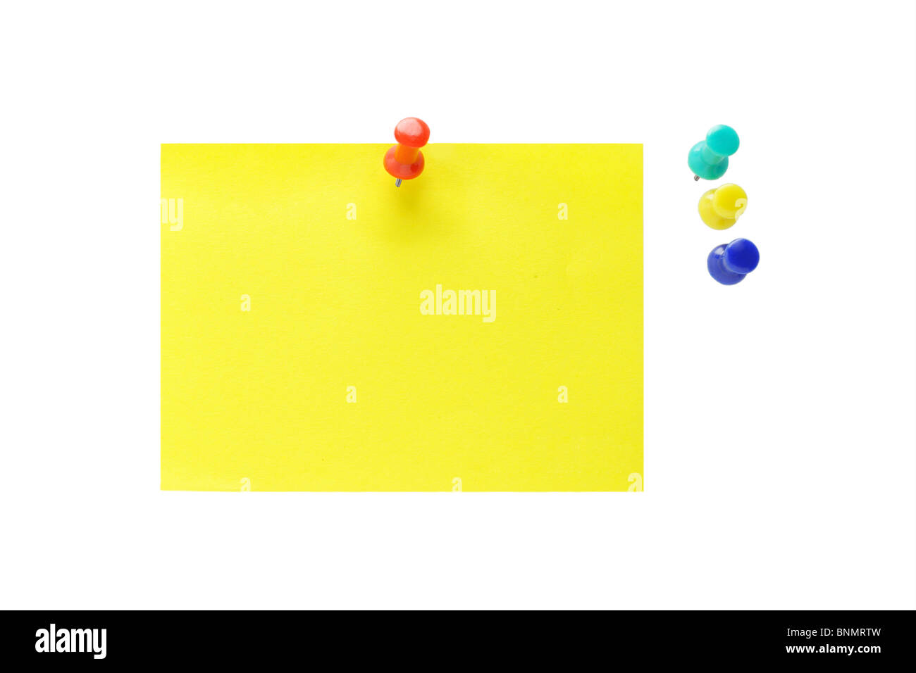 Multicolor push pins and yellow note paper on white background - Stock Image