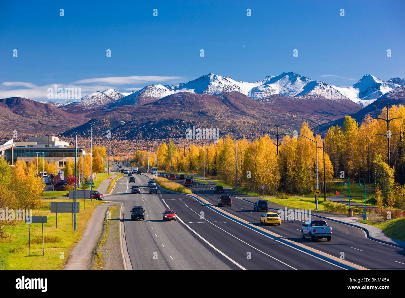 Traffic on Tudor Road looking east towards the Chugach Mountains during Autumn, Anchorage, Alaska - Stock Image