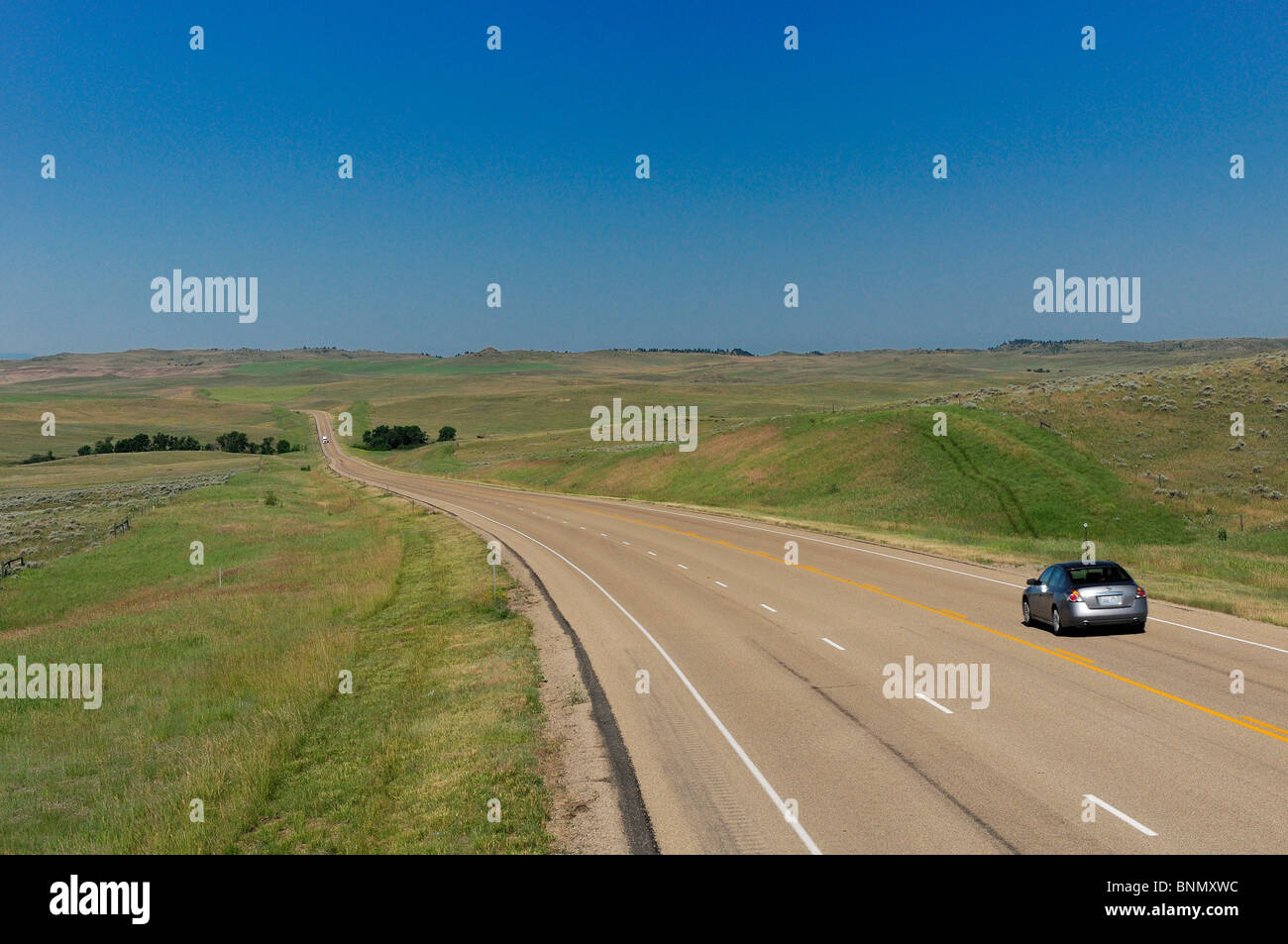 Car Highway 212 Crow Agency Crow Indian Reservation Montana USA fields - Stock Image