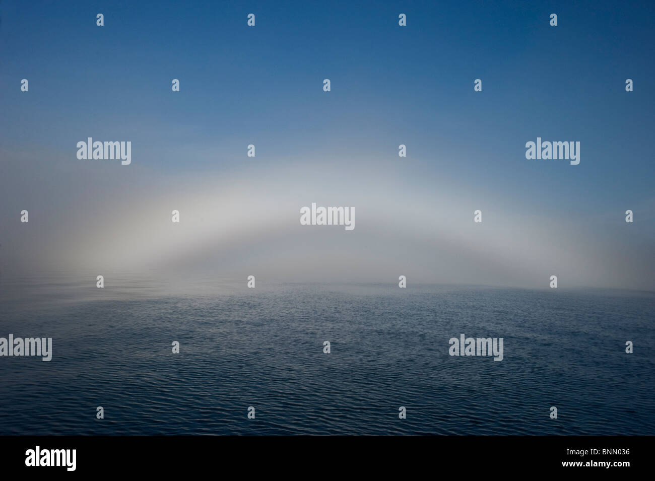 A fogbow appears over the horizon in Prince William Sound during Autumn in Alaska - Stock Image